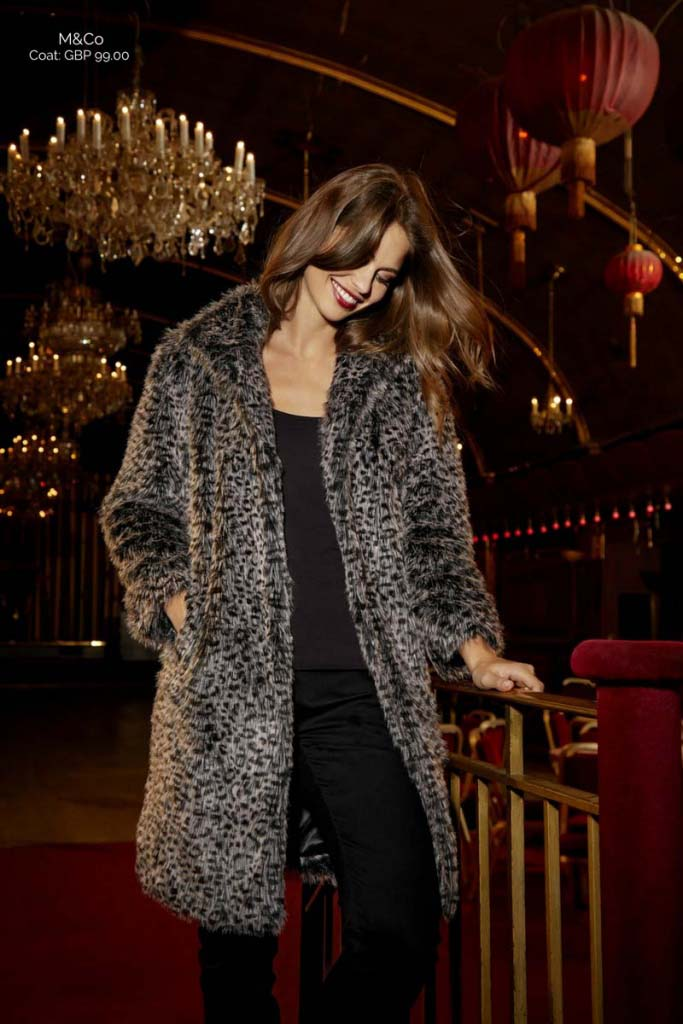 A beautiful young woman model wearing a leopard print coat. Image by M&Co.