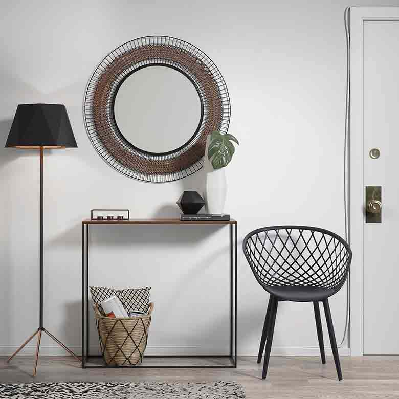 The black Zayna armchair next to this slender frame console table really gives a contemporary edge to this minimal entryway. A black shade floor lamp adds that inky stain that balances the armchair. Image by Cuckooland.