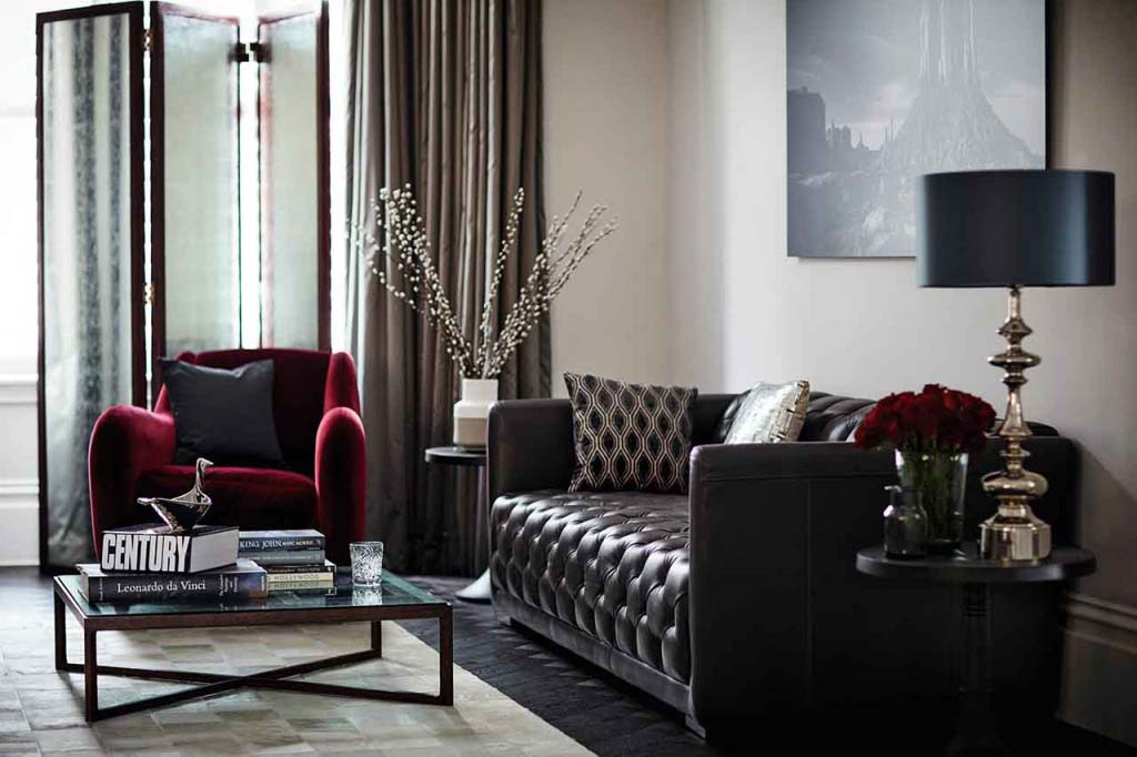 A stylish living room with a dark leather sofa and a deep burgundy velvet armchair with a coffee table in the middle. The hardwood flooring is stained really dark and there are greige velvet curtains by the window door. Image by DFS Furniture.