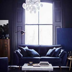What a cinematic and moody ambiance in this stylish living room, with its blue sofa being flooded by the sunlight from the door window behind. Image from DFS Furniture.