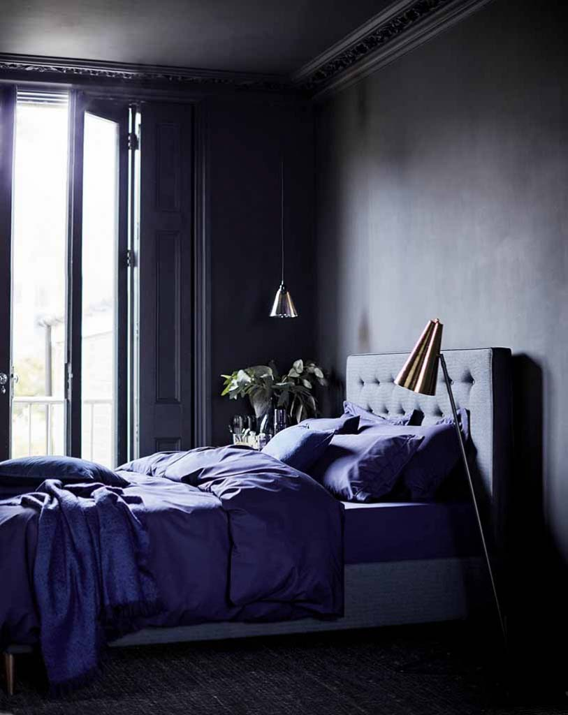 A moody dark purple bedroom with a dark ceiling, a purple bed stand, purple bedding, a nightstand with a plant on the one side and a copper pendant light over it, while on the other side there's a copper floor lamp. The window doors is open letting the light breeze in the room creating a sexy ambiance.