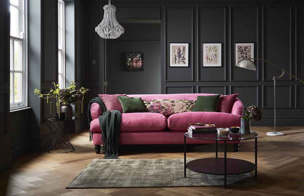 A moody interior with dark grey walls, hardwood flooring, a crystal chandelier and a pink velvet sofa with hunter green velvet pillows in contrast. The ensemble is completed with a round coffee table on the side over a light colored pattern area rug. Photo by DFS Furniture.