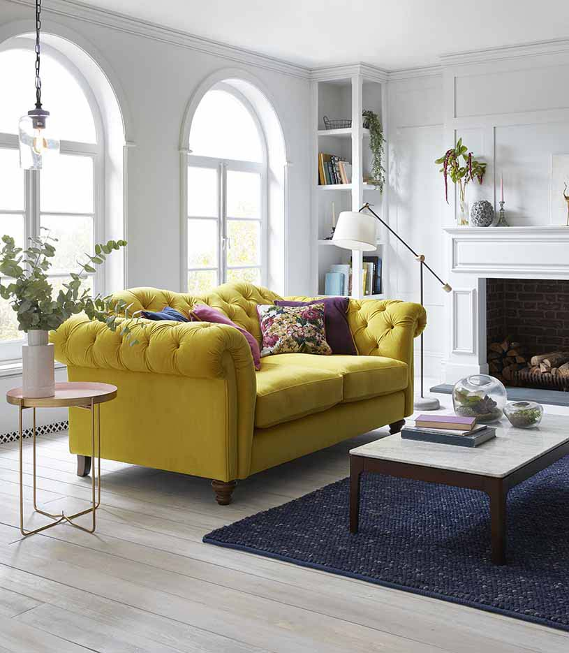 A beautiful sofa in a mimosa hue is definitely a head turner in this white interior. Image by DFS Furniture Co.