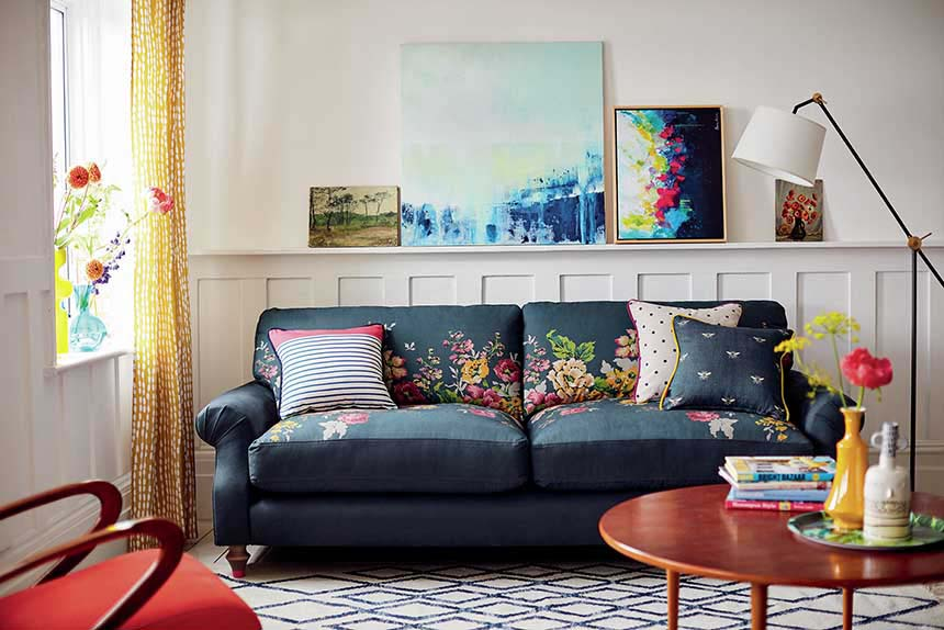 What a joyful living space with that blue sofa and its flower pattern that surprisingly isn't overwhelming. Instead it is combined with other pattern pillows and a rug, giving a twist. Image by DFS Co plc.
