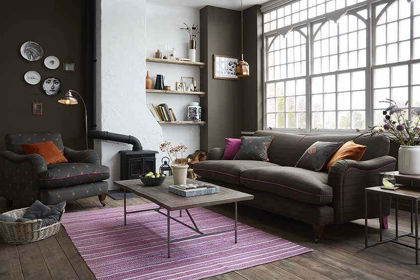 Loving a moody interior with a dark Ilkey sofa being jazzed up by a pinkish flatweave with a geometrical pattern area rug under a minimal coffee table. Image by DFS Co. Plc