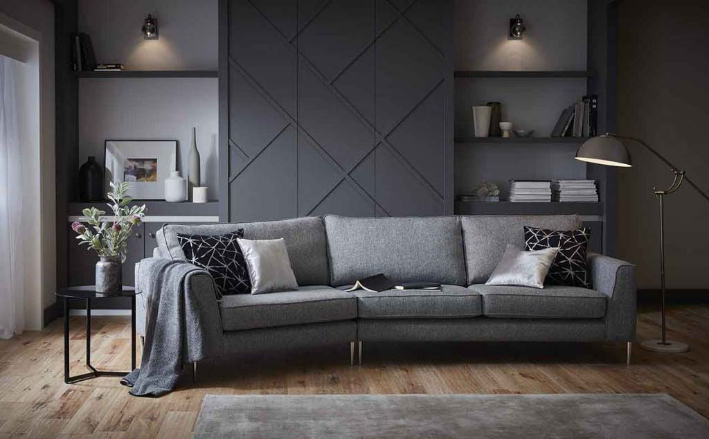 A contemporary moody living room set in dark grey hues, a grey sofa, hardwood flooring and two built-in shelf units behind, creating focal features in a minimal way and accentuating the curvy line of the sofa. The floor lamp besides the sofa and the scones on the wall behind help create a cozier atmosphere. Image from DFS Furniture.