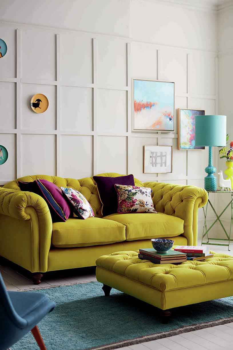 A very stylish living room interior with purple, fuchia and pattern throw pillows on a lime colored sofa and ottoman really standing out as a statement. The ensemble is completed with a turquoise table lamp on a steel side table standing in front a small art gallery wall.