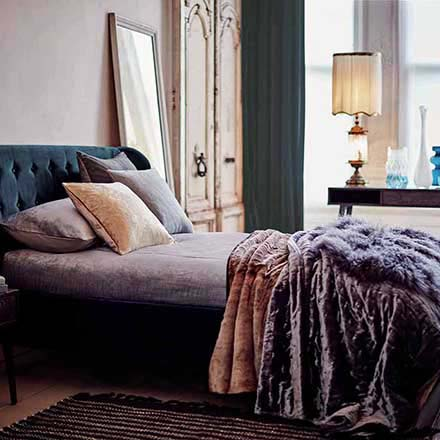 A beautiful bed stand in blue teal and purple bedding and lush throws in a very stylish bedroom with blush pink and teal hues.