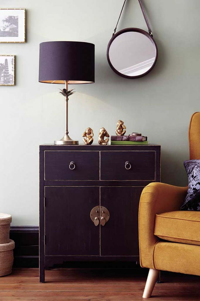 A black Chinese chest looks great against a minty color accent wall and a mustard yellow armchair at the side. A black shade table lamp and brassy decor and a round mirror hanging from the wall, make a stylish ensemble. Image by Dunelm.