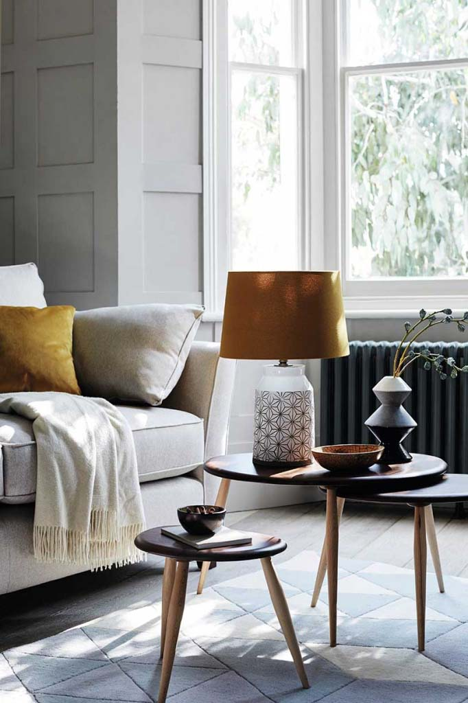 A neutral off white interior gets more lively from a mustard yellow cushion on the off-white Bond sofa, while a nest of three tables with a table lamp and a lampshade in a burnt sienna hue fill in nicely the natural and neutral palette. Image by Furniture Village.