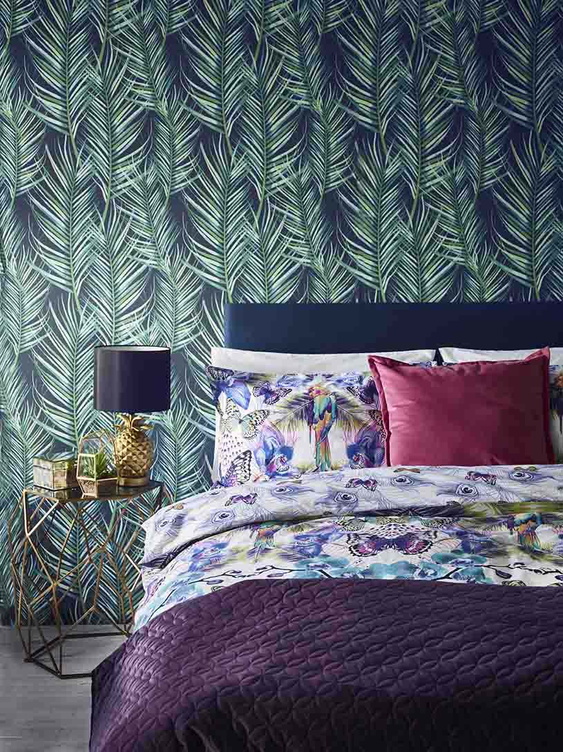 A stylish bedroom with a blue bed headboard, pattern bedding, a purple throw at the end of the bed, a brass night stand with a pineapple table lamp on it. All these are featured in front of an accent with with a palm tree leaf pattern against a blue purple background wallcovering. Wow!