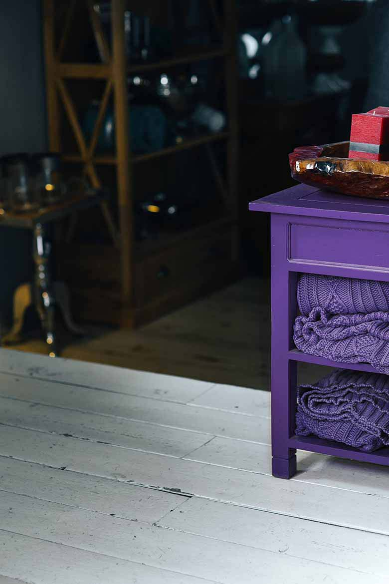 A small purple night stand with shelves and purple knitted throws tucked under