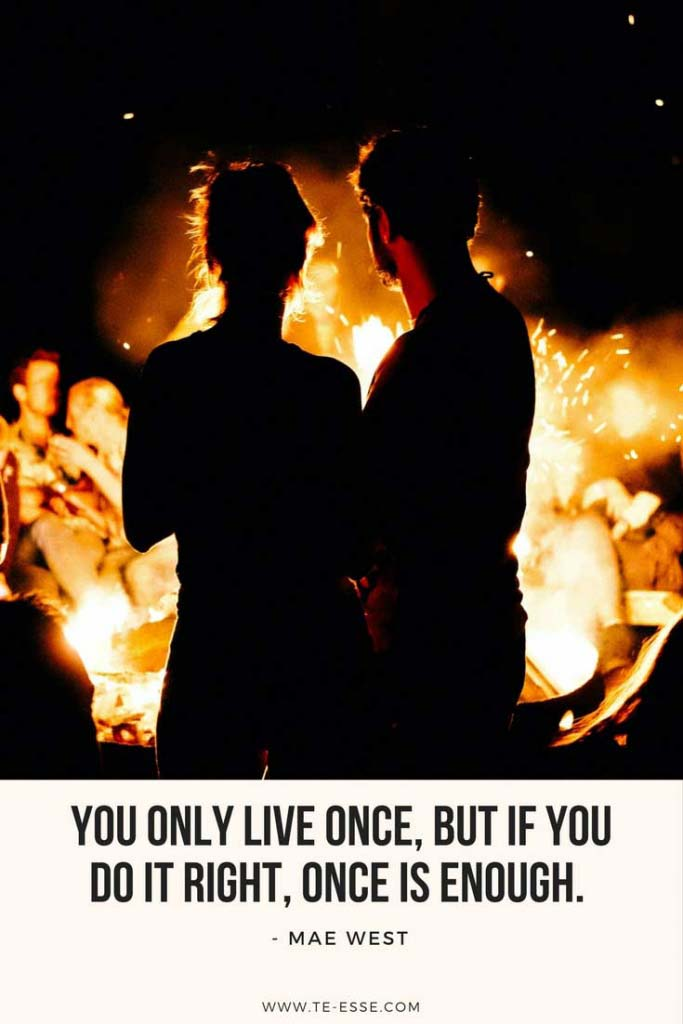 A beautiful shot of the silhouettes of a couple looking at a fire with a quote under it saying You only live once, but if you get it right it's enough cited from Mae West.