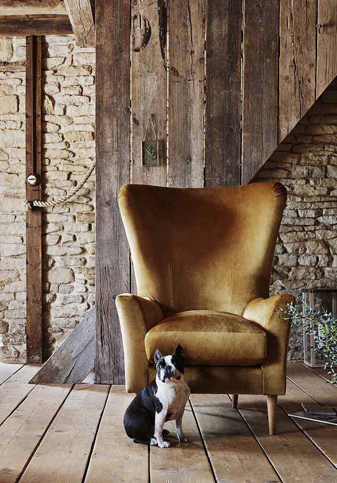 What a gorgeous armchair in a velvet ochre yellow, in contrast to the earthy colors and organic materials (stone and wood) that dominated this space. Image by Next.co.uk.