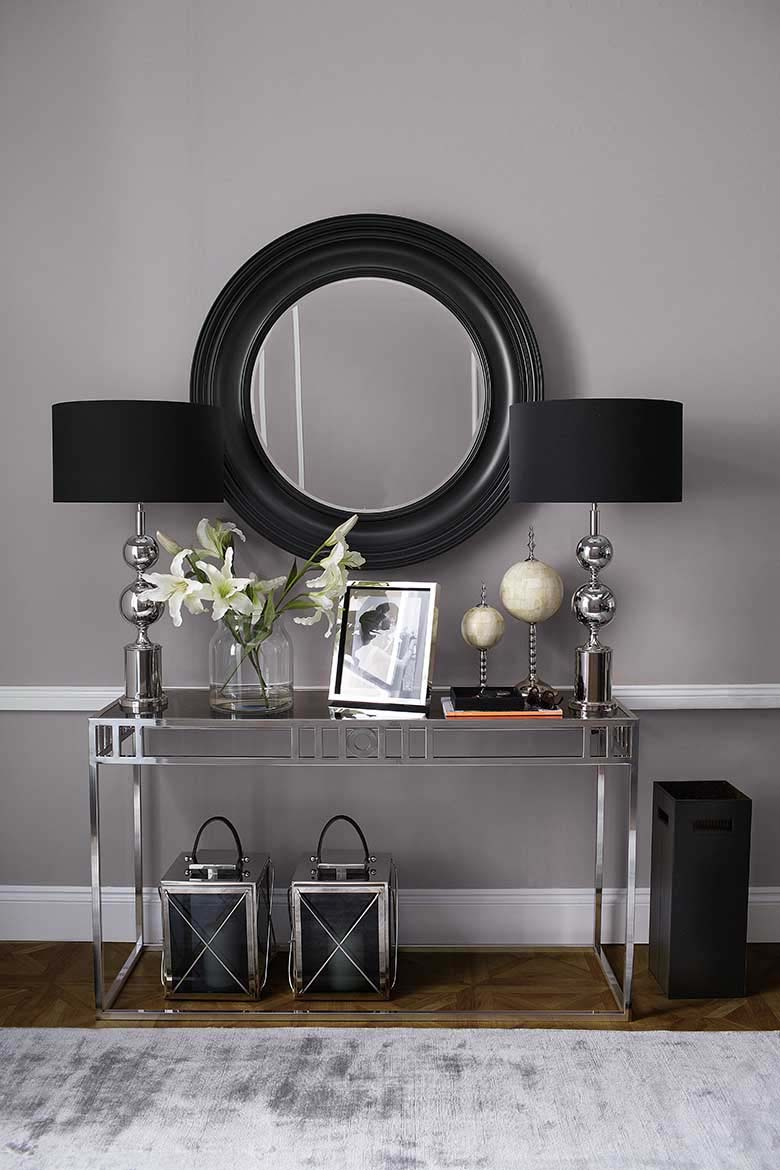 A stunning looking chrome finish Andrew Martin De Luna Console Table styled with frames, a vase and lanterns and a large round dark mirror over it. Image by Houseology.