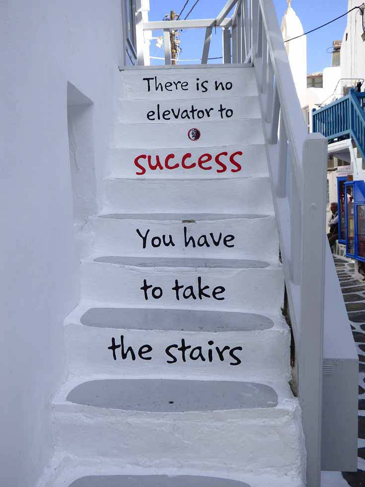 """What a cool idea. A photo of a white washed staircase in a Greek island. A quote that reads """"There is no elevator to success. You have to take the stairs is written on the rise of each step."""