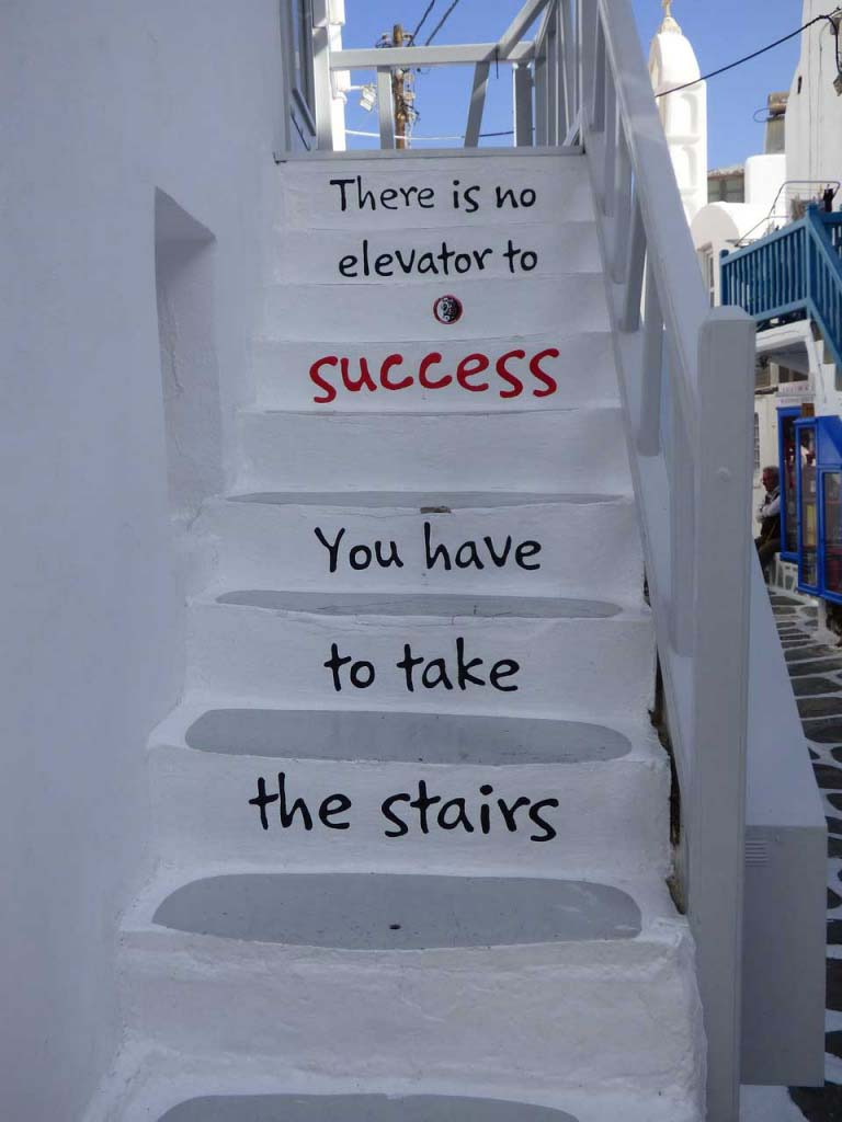 "What a cool idea. A photo of a white washed staircase in a Greek island. A quote that reads ""There is no elevator to success. You have to take the stairs is written on the rise of each step."