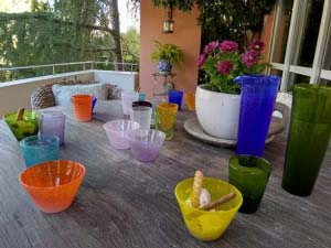 A bunch of colorful Murano bowls and glasses that Elisabeth bought on her honeymoon and brought home.