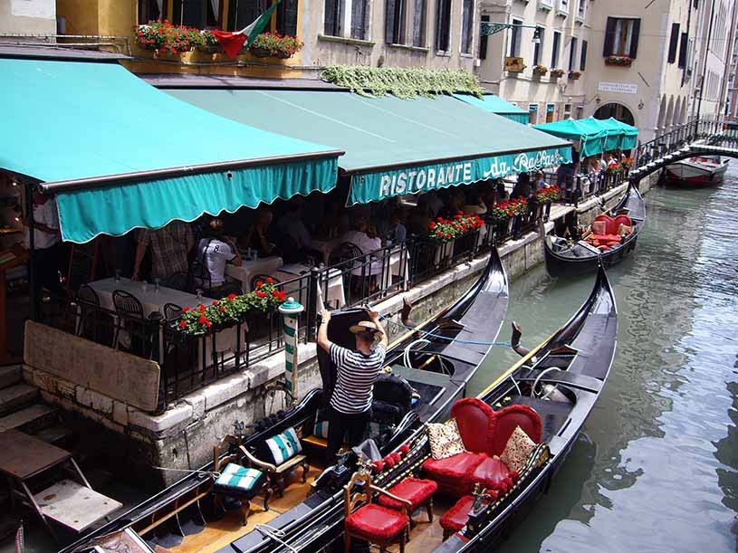 Gondolas docked to the side of a bank for people from the a restaurant to embark or disembark, in Venice.