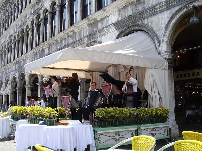 Musicians playing music under a stand with a canopy in St. Mark's Piazza in Venice.