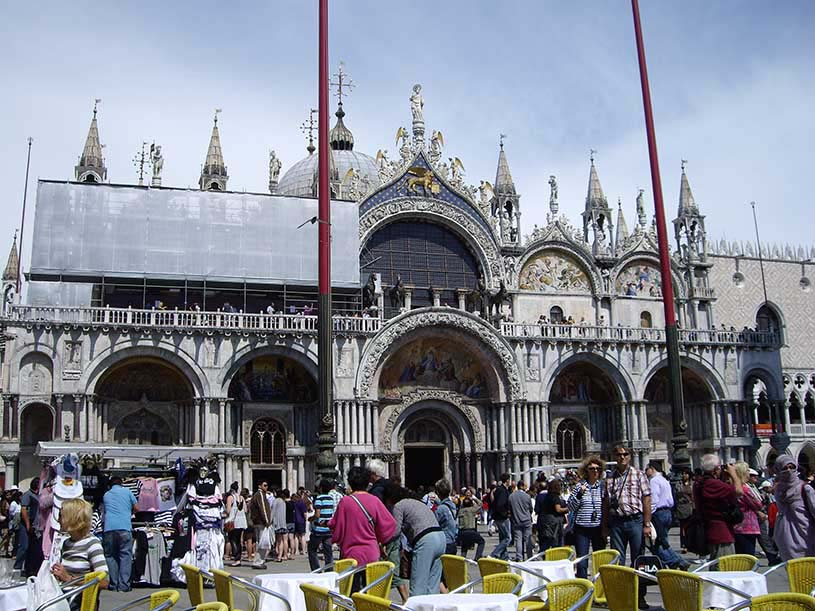 View of St. Mark's Basilica in Venice, crowded with people.
