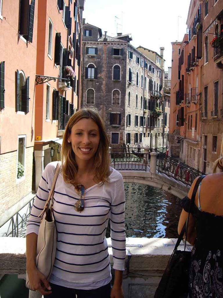 Elisabeth on a bridge in Venice with a canal in the background.