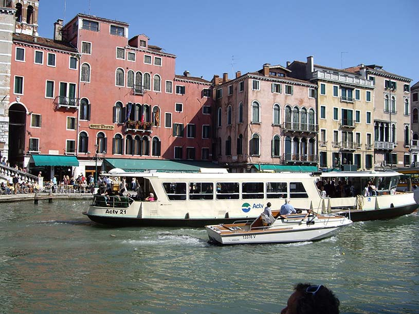View of river taxis and boats sailing along the Grand Canal, with colorful buildings in Venice.