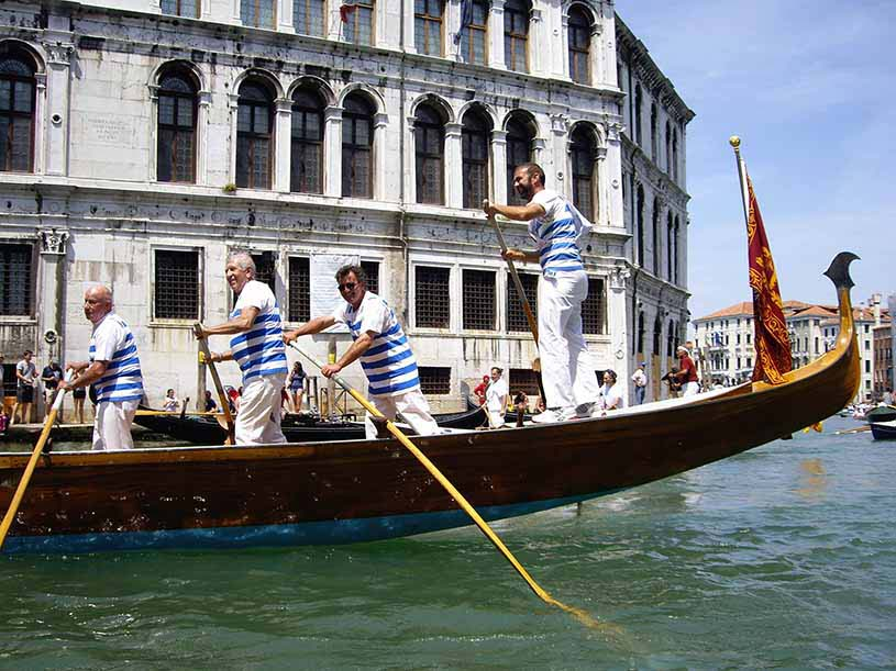 During a race, gondoliers rowing away in the Grand Canal.