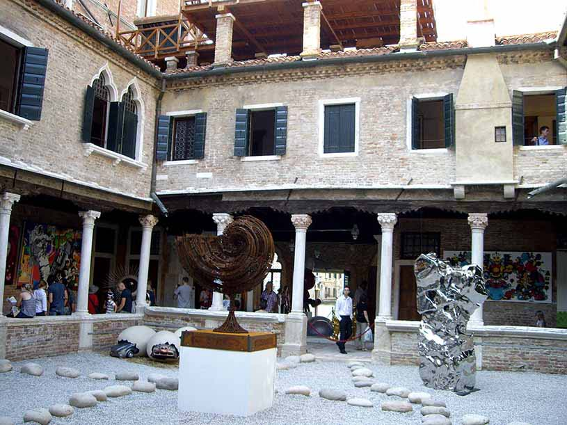 Inside the yard of the Peggy Guggenheim Museum with several sculptures in open display for viewing.