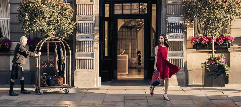 A young woman dressed in a red dress walks out of an old classy building full of confidence. Image by Barbour.