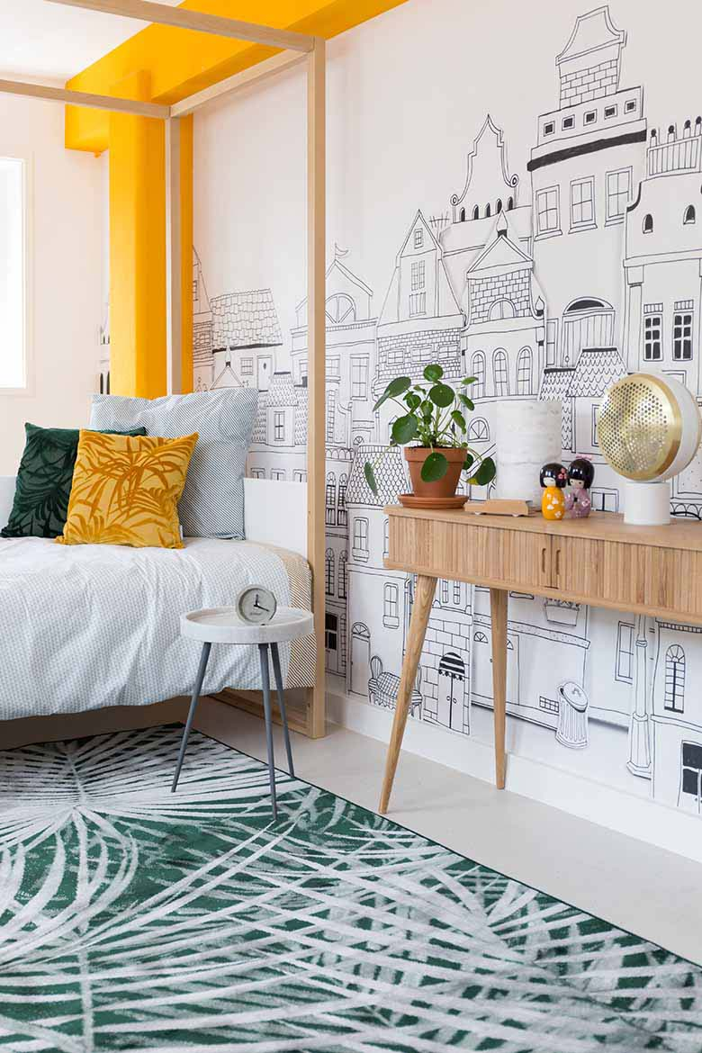 A bright bedroom looking stunning due to a beam-column yellow blocking, an inky wall mural and a green pattern motif area rug. Image by Cuckooland.