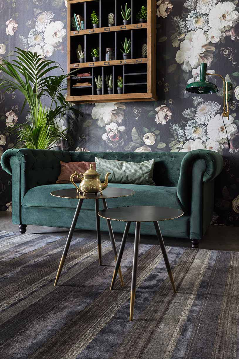 A stylish, moody living room with a gorgeous green velvet sofa against a dark floral motif wallpaper. Image by Cuckooland.