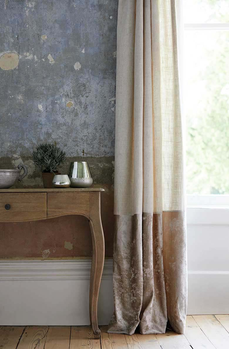 What an awesome detail of a console table by a door window. Both the wall and the curtain are color blocked in muted terracotta shades. Very French. Image by Dunelm.