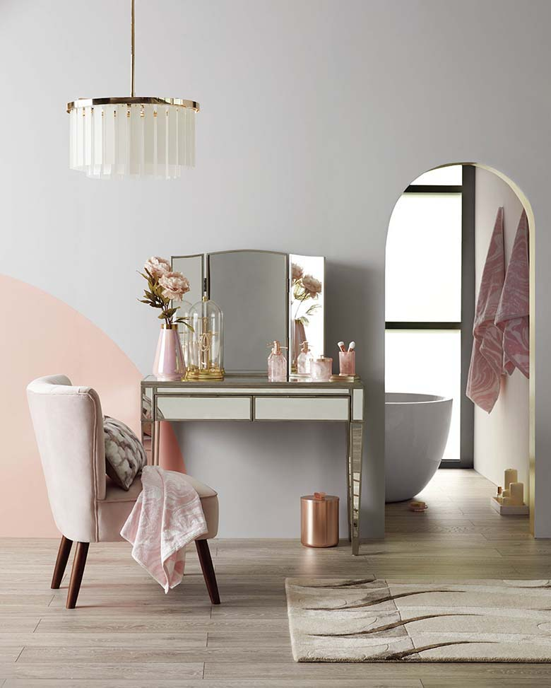 A stylish boudoir with pink and grey color blocking on the wall. Love the copper and brassy details of the furniture that add on a lux sense. Image by Dunelm.