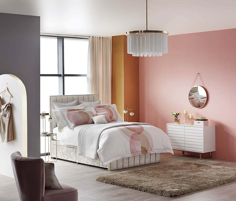 A feminine bright bedroom with pink, muted mauve, and mustard color blocked walls. Very stylish indeed. Image by Dunelm.