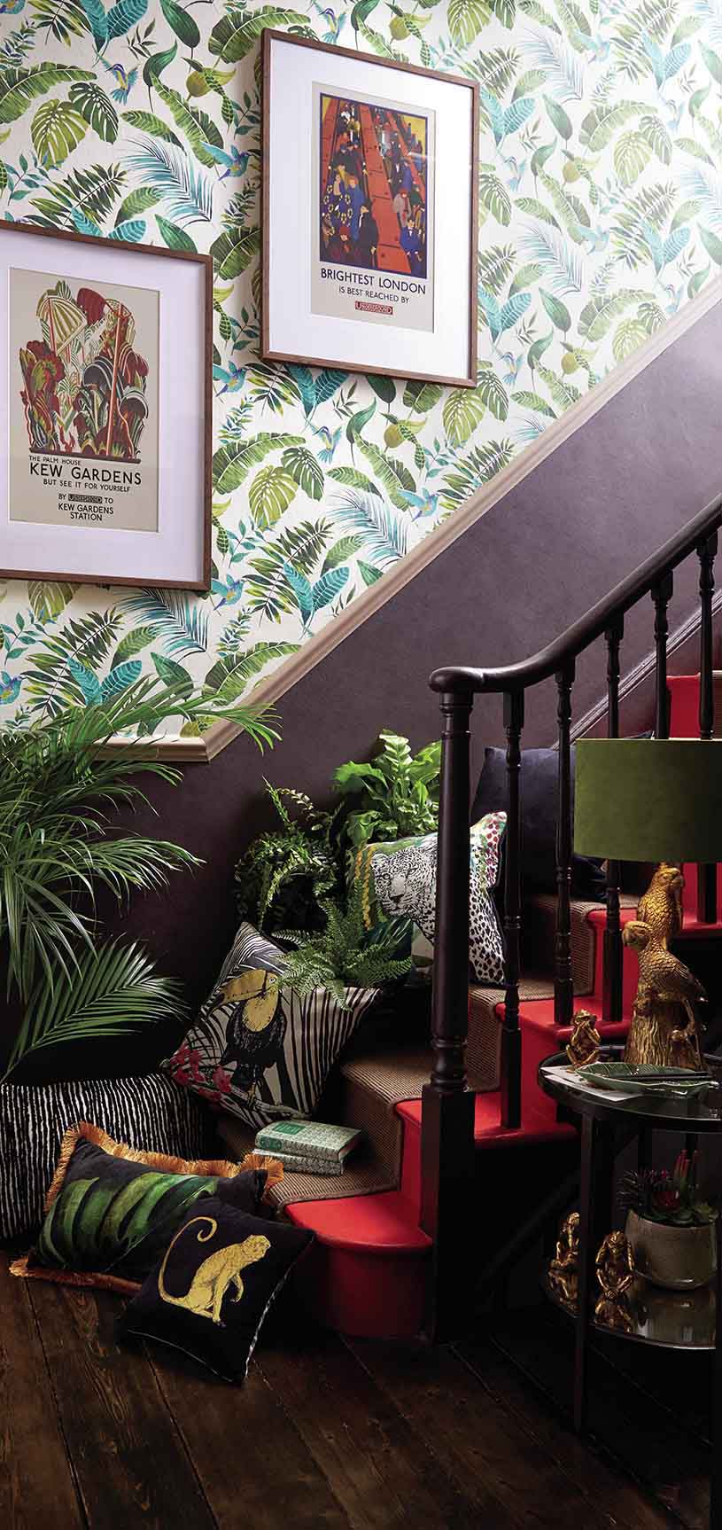 What a vibrant staircase thanks to a green foliage motif wallpaper, a number of plants and two image prints. Image by Dunelm.