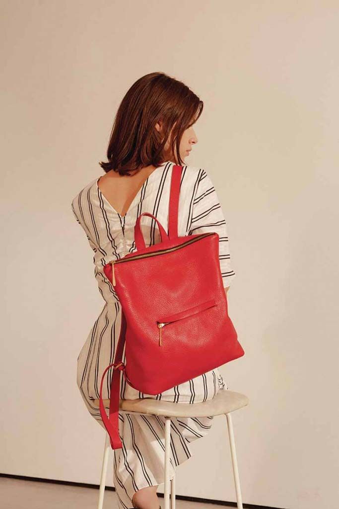 A beautiful red leather backpack by Jigsaw, carried by a young woman model.