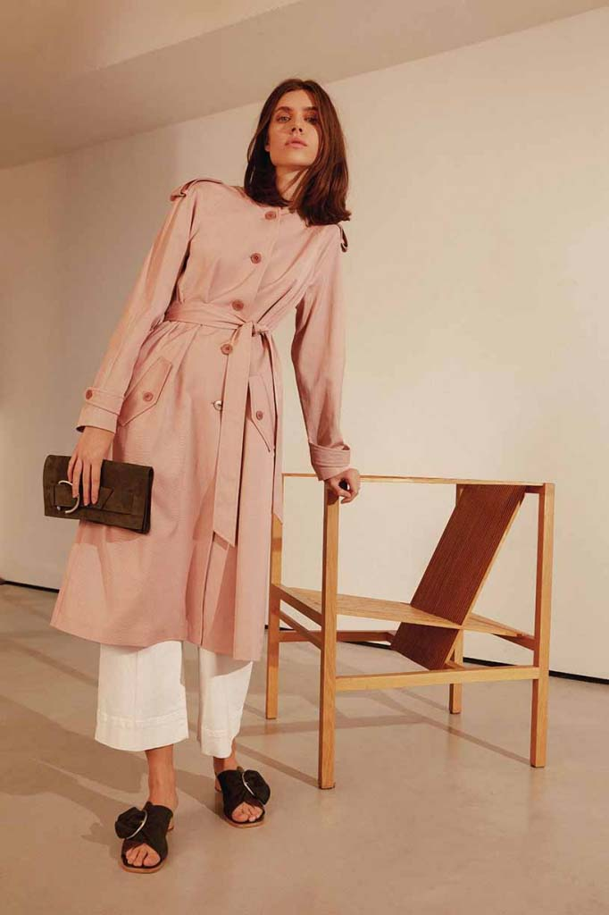 What a great trench coat in a peachy pink combined with white loose pants and flat sandals. Image by Jigsaw.