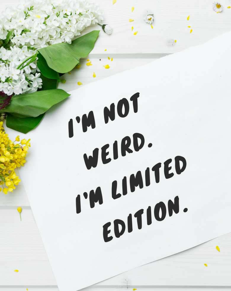 I'm not weird. I'm limited edition. Quote appearing on a piece of paper from a flatlay image.