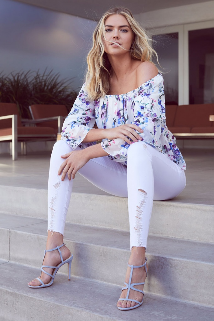 A white with floral print Bardot top will always look this great when paired with a white pair of distressed denims and high heel sandals like with this beautiful model. Image by Lipsy London.