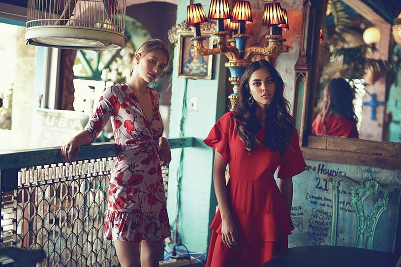 Two gorgeous dresses worn by models - a red one and a pink with red motif. Image by Little Mistress