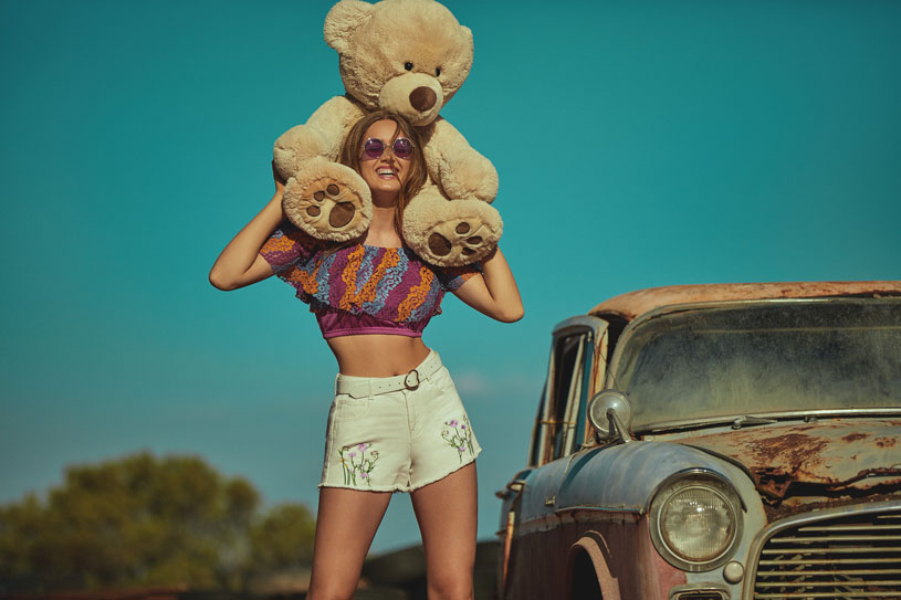 A pretty model is holding a huge teddy over her shoulders while wearing a cropped Bardot top and a pair of white shorts. Image by Girls on Film.