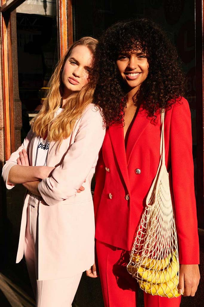 Two models - a blonde woman dressed in a pink power suit and a brunette dressed in a red power suit. Image by Miss Selfridge.