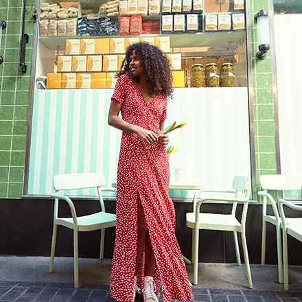 A pretty long red dress with white polka dots worn by a young model with a casual style. Image by Miss Selfridge.