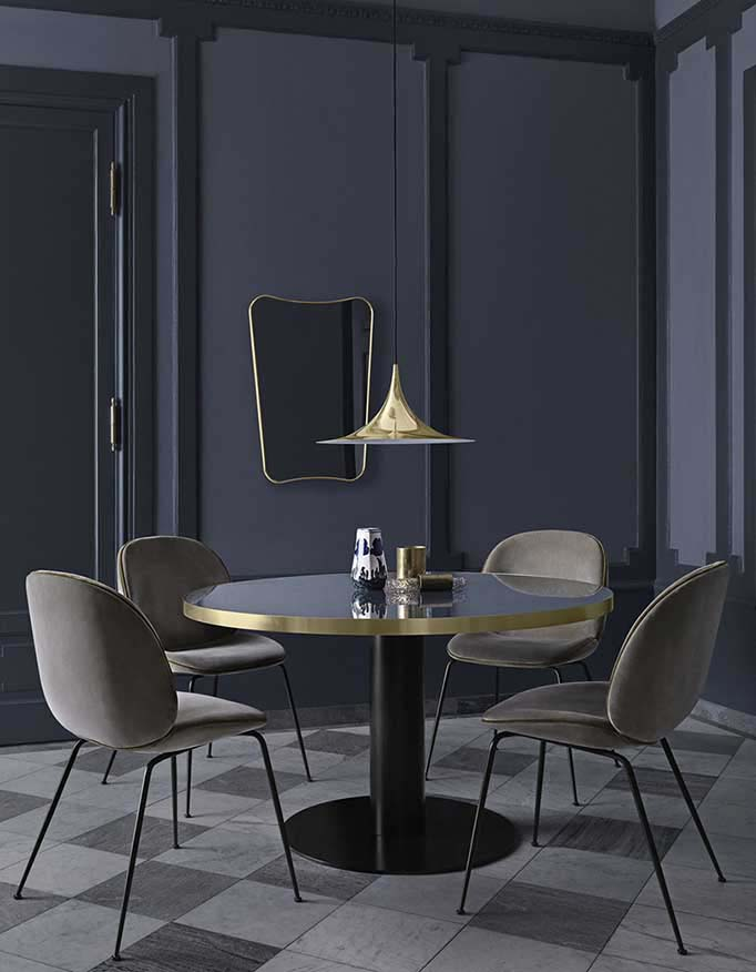 Proof that a brass pendant Gubi light can upgrade a dark moody dining space. The brass finish of the light matches the brass finish of the dining table's perimeter. A beautiful touch. Image by Nest.co.uk.