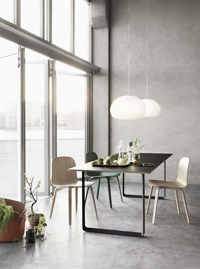 A warm glow transcends this contemporary dining space due to the two Muuto white pendant lights. Image by Nest.co.uk.