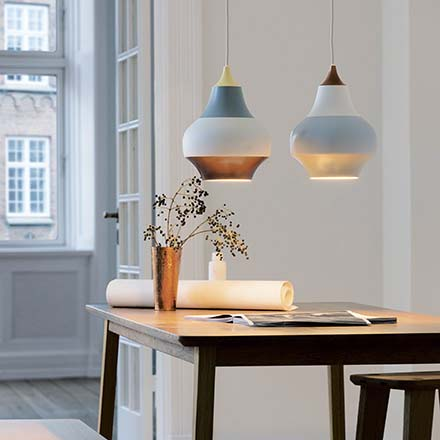 Two beautiful Louis Poulsen pendant lamps over a dining table create a hygge ambiance. Image by Nest.co.uk