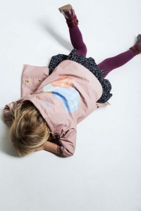 A beautiful soft pink raincoat worn by a little girl who's lying on the floor makes a great statement in her outfit.