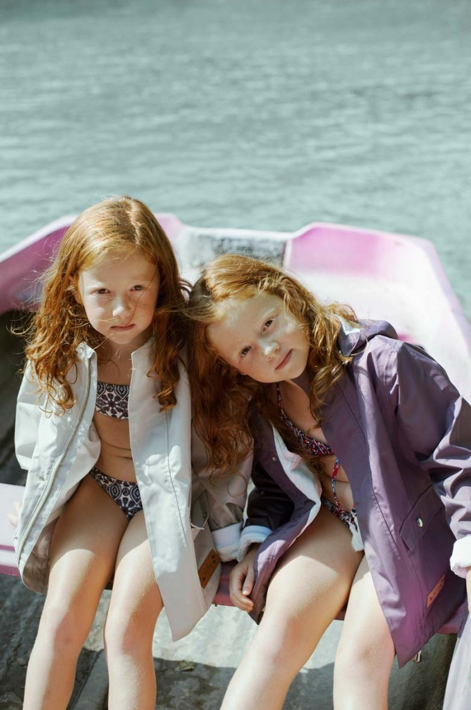 Two young twin sisters wearing swim suits and raincoats sit in a small boat by the water.