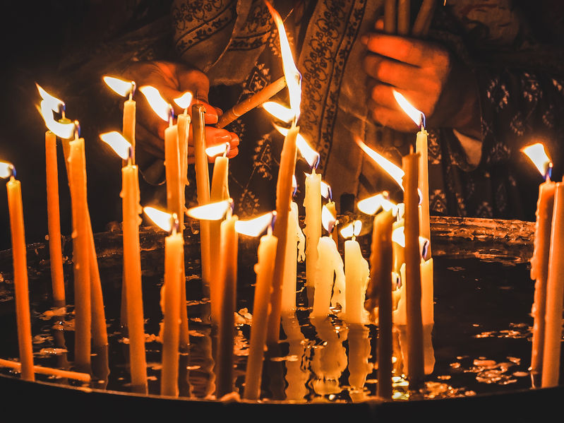 A woman lighting a candle inside an Orthodox Christian church.